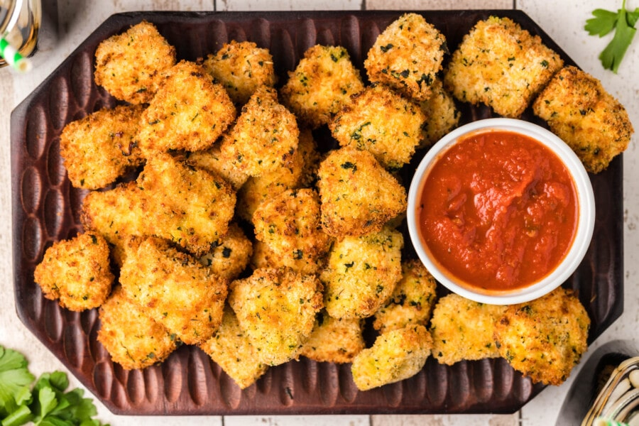 Overhead shot of air fried popcorn chicken with bowl of dipping sauce on serving tray