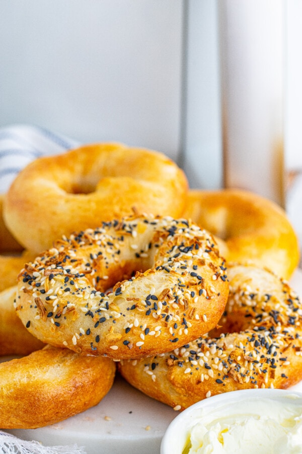 Air fryer bagels stacked atop one another on white plate