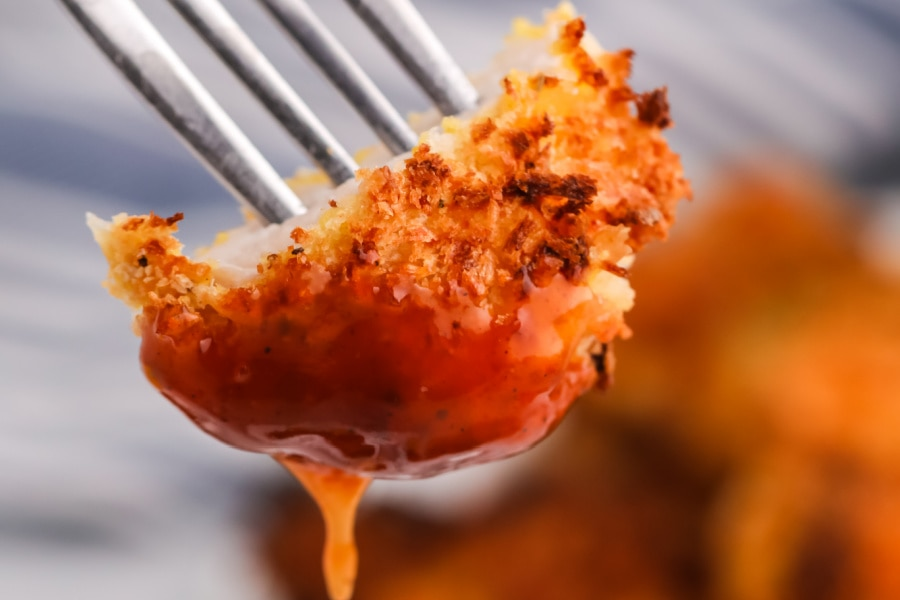 Closeup shot of piece of air fryer fried chicken thighs on fork dipped into sauce