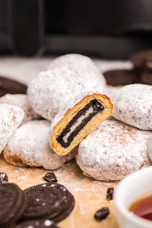 Air fried Oreos on wooden table with one Oreo cut in half