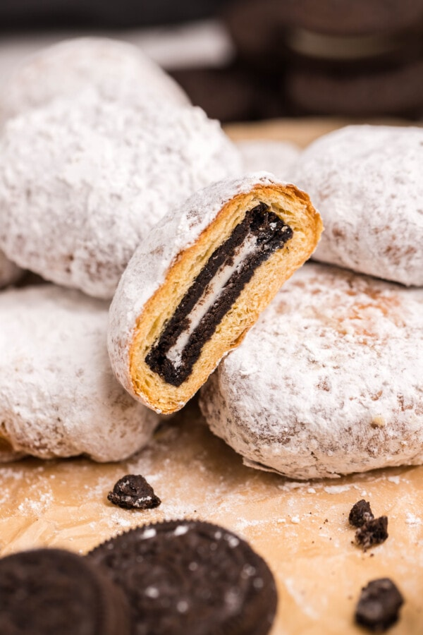 Close up of air fryer fried Oreos on wood cutting board with one Oreo cut in half