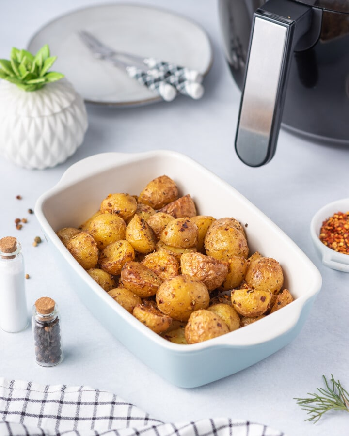 a white casserole dish filled with air fryer baby potatoes
