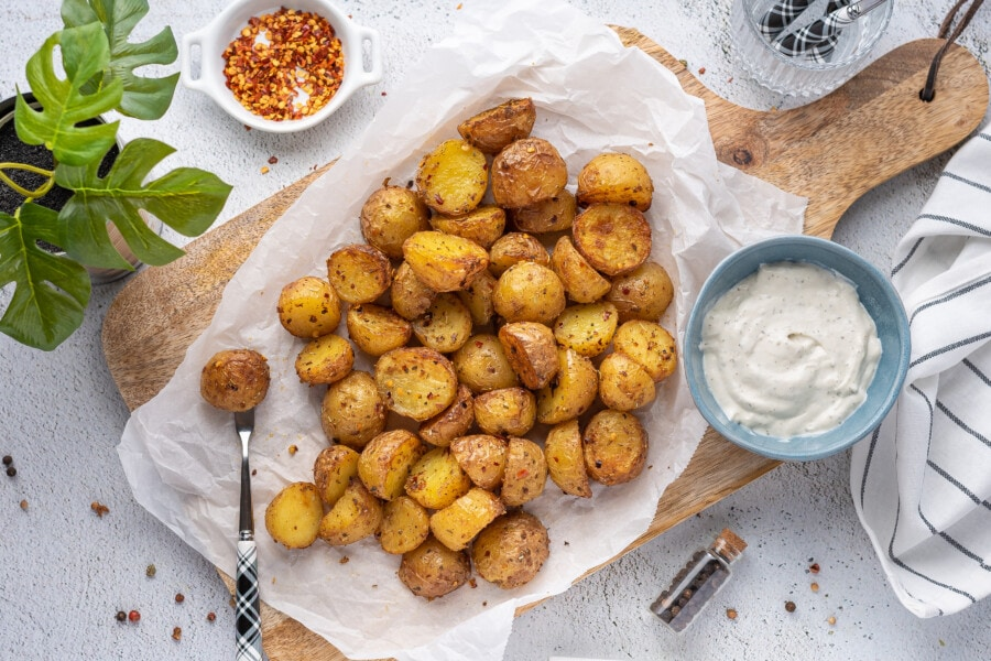 rustic overhead photograph of little potatoes cooked in an air fryer with dip and red pepper flakes in bowls on the side