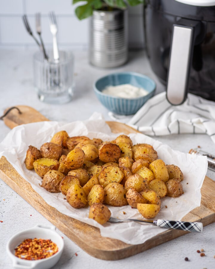 crispy mini potatoes fresh out of the air fryer sitting on a piece of parchment paper on a cutting board