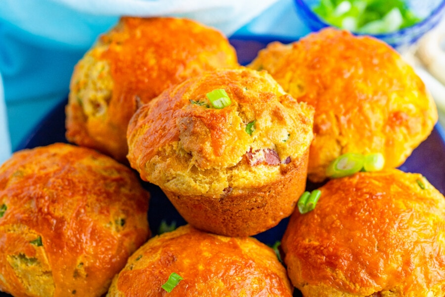 A pile of Corn Muffins in a bowl with a closeup of the corn muffin in the center.