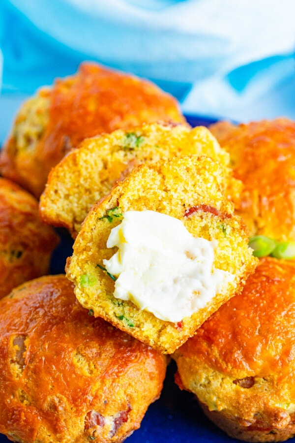 A pile of Jalapeno corn muffins with one sliced and buttered on top.