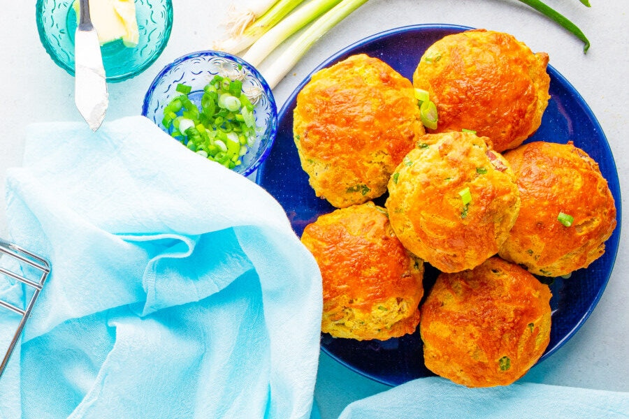 Plate full of Homemade corn muffins with butter and a knife beside it, some green onions and a blue scarf.