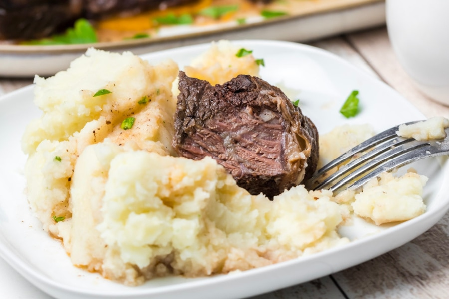Instant pot beef short ribs with mashed potatoes on white plate