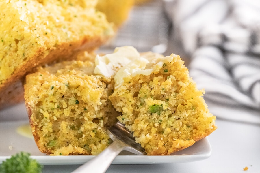 close up shot of broccoli cornbread on a white plate with a silver fork