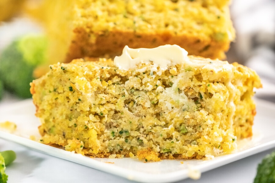 two pieces of brocolli cheese cornbread on a white square plate topped with butter