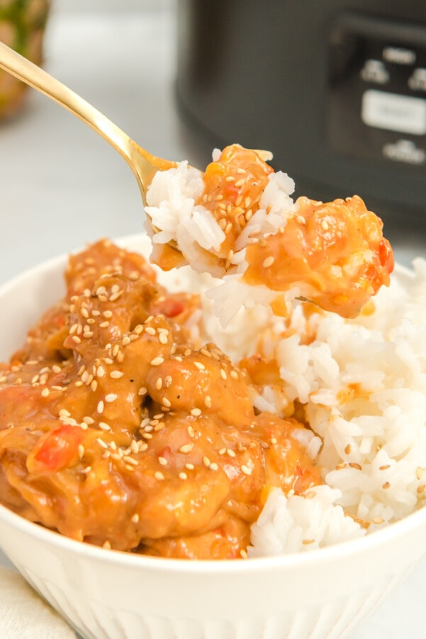 close up shot of pineapple chicken on gold fork with white rice. A blurry slow cooker in background.
