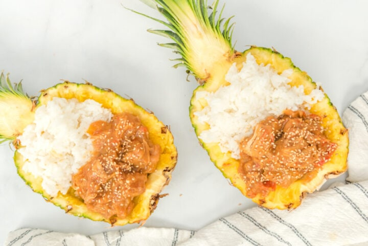 two slightly off center pineapple halves filled with pineapple chicken and white rice next too white and gray towel.