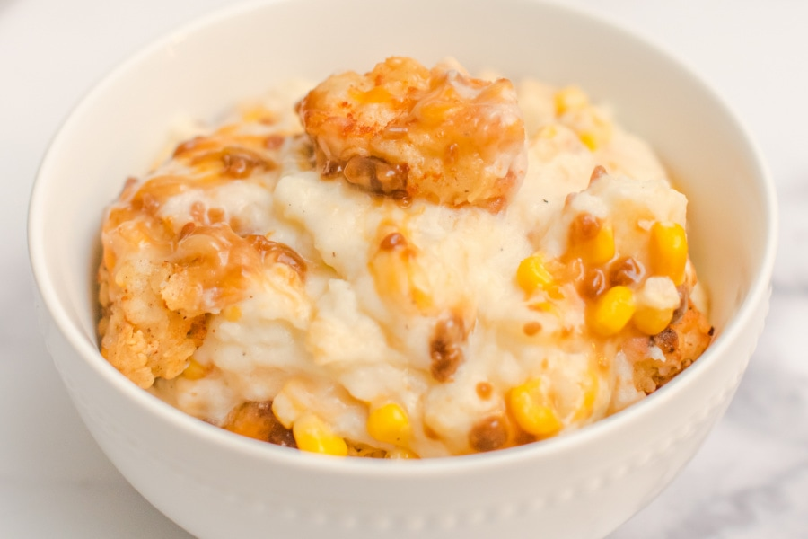A white bowl filled with mashed potatoes, corn chicken bites, gravy and cheese.