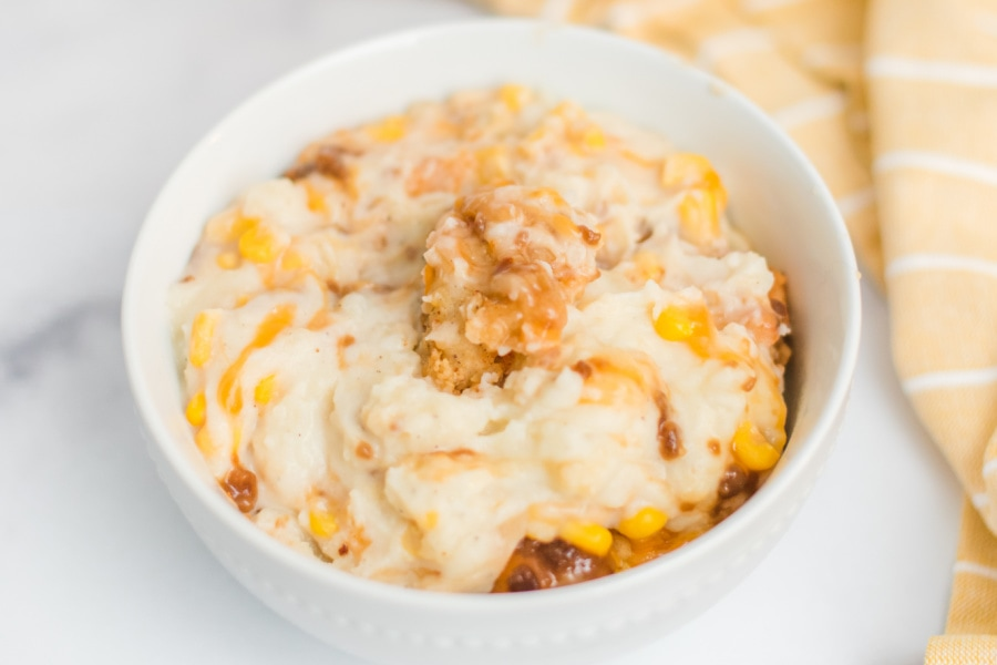 A shot of KFC Chicken bowl filled with mashed potatoes, corn, gravy, cheese and a crispy chicken nugget on top.