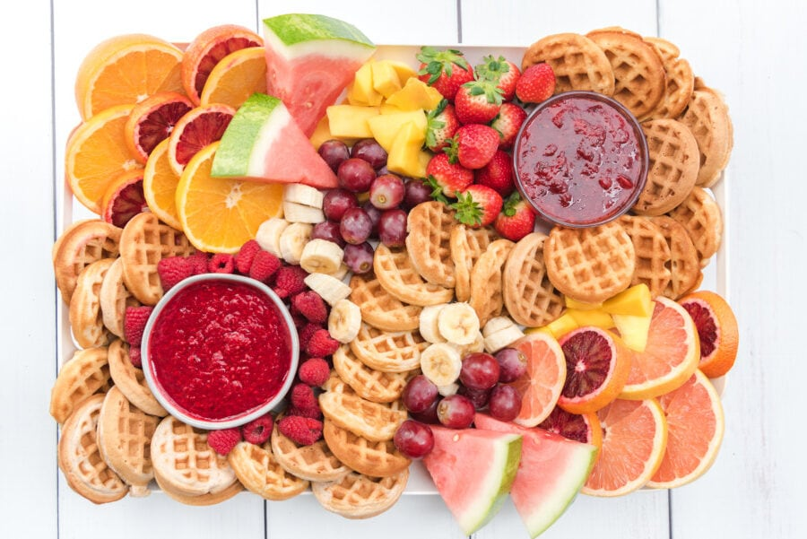 Breakfast charcuterie board or brunch charcuterie board filled with mini waffles, fresh fruit and strawberry and raspberry dipping sauces.