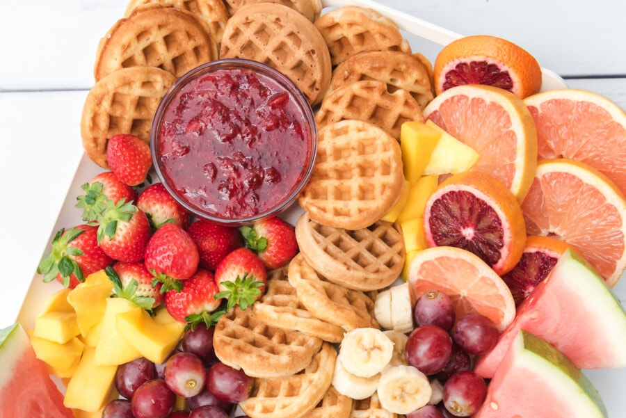Half of a breakfast board full of waffles, raspberry sauce, strawberries, pineapple, grapes, bananas and watermelon.