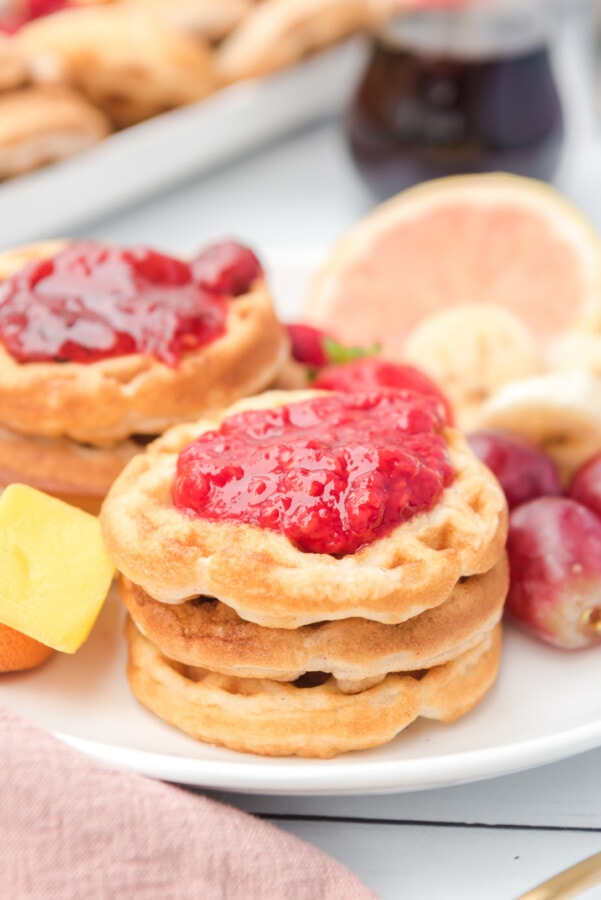 A closeup of three waffles piled up covered in strawberry sauce on a white plate with grapes, more waffles and grapefruit.