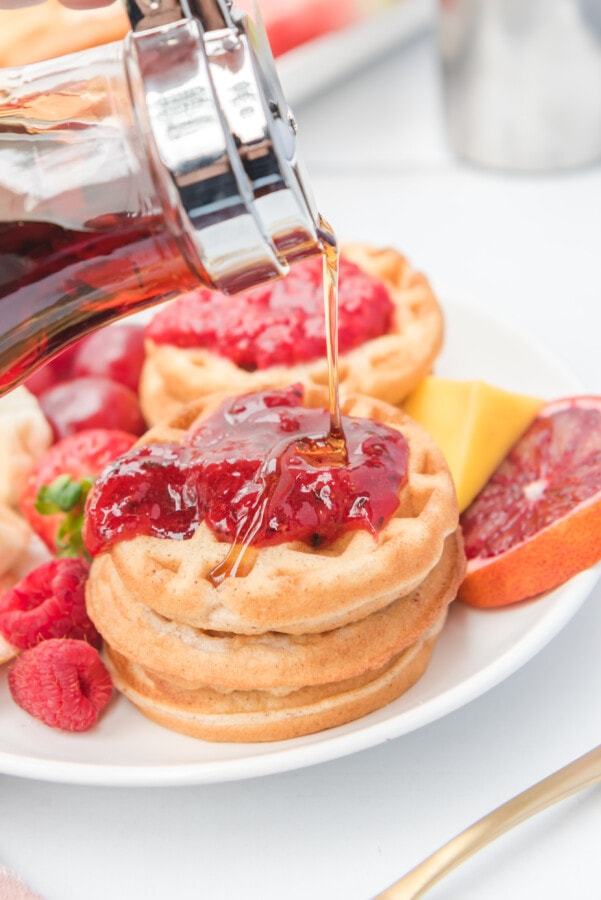 Syrup being drizzled on top of a stack of mini waffles covered in strawberry sauce and fresh fruit to make a brunch charcuterie board