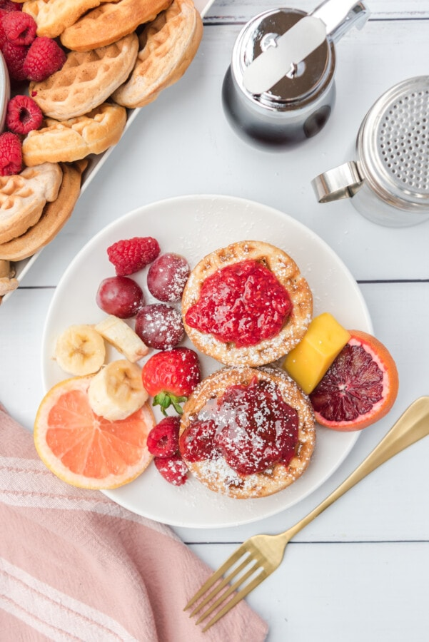 Overhead shot of a couple waffles with raspberry and strawberry sauce, fresh fruit with a dusting of powdered sugar on a breakfast charcuterie board