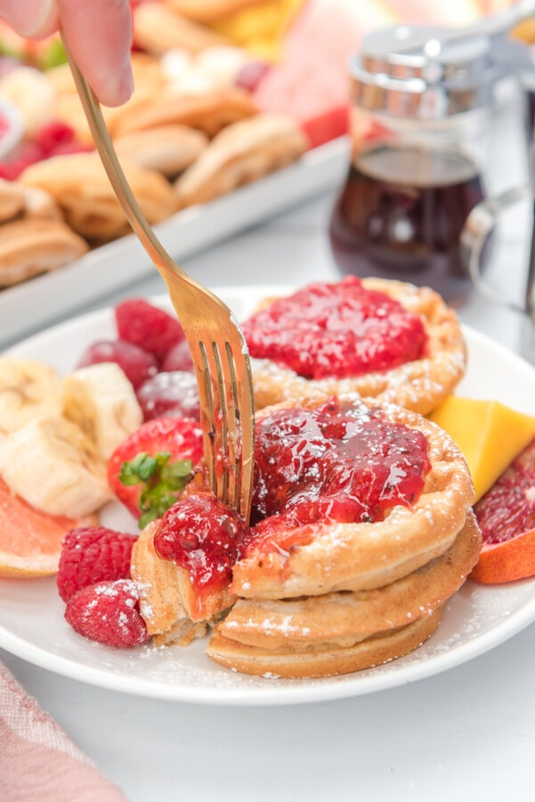 White plate with waffles and strawberry sauce being sliced by a fork.
