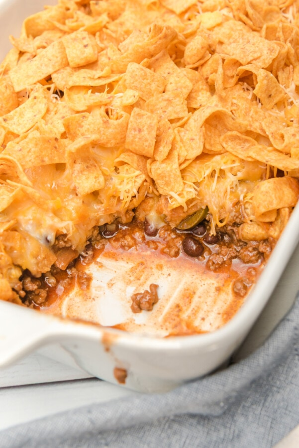 Closeup shot of taco bake with Fritos in baking dish with spoonful removed