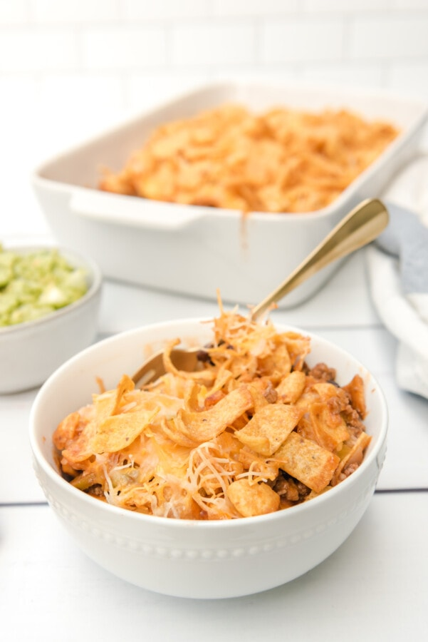 Closeup shot of bowl filled with taco bake with Fritos with more Frito casserole in background