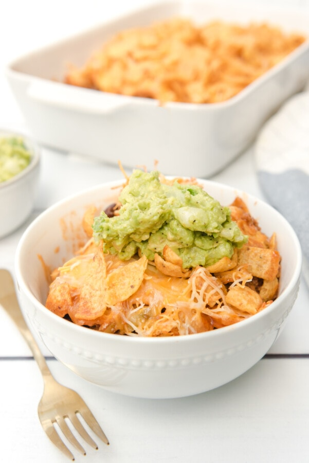 Closeup shot of taco bake topped with guac in bowl with more taco bake in background
