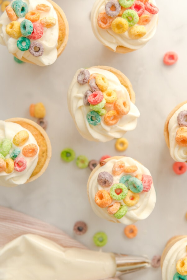 Overhead photograph of cupcake cones baked and topped with icing and Fruit Loops
