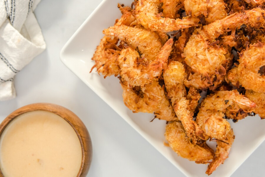 Overhead shot of air fried coconut shrimp on white hplate next to bolw of pina colada sauce