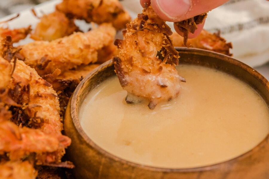 Closeup shot of fried shrimp being dipped into bowl of dipping sauce.