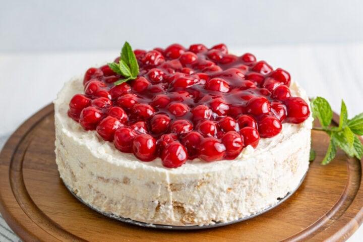 No bake cherry cheesecake icebox cake on wooden stand