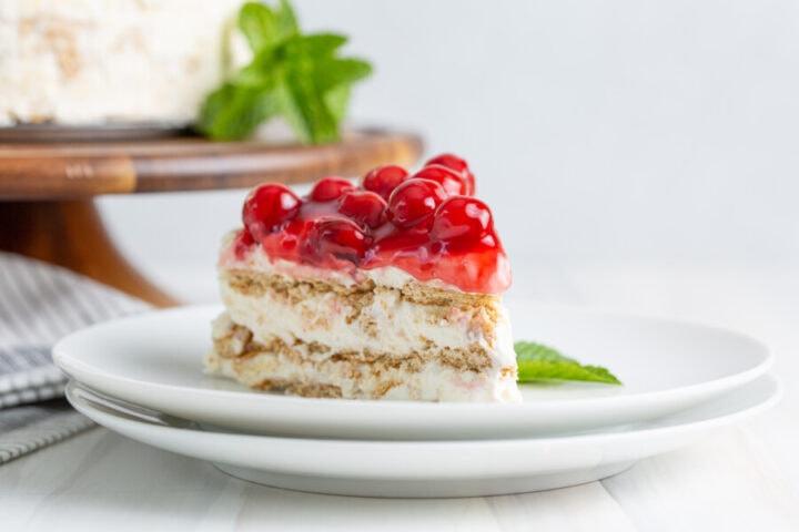 Closeup shot of slice of no bake cherry cheesecake icebox cake on white plate