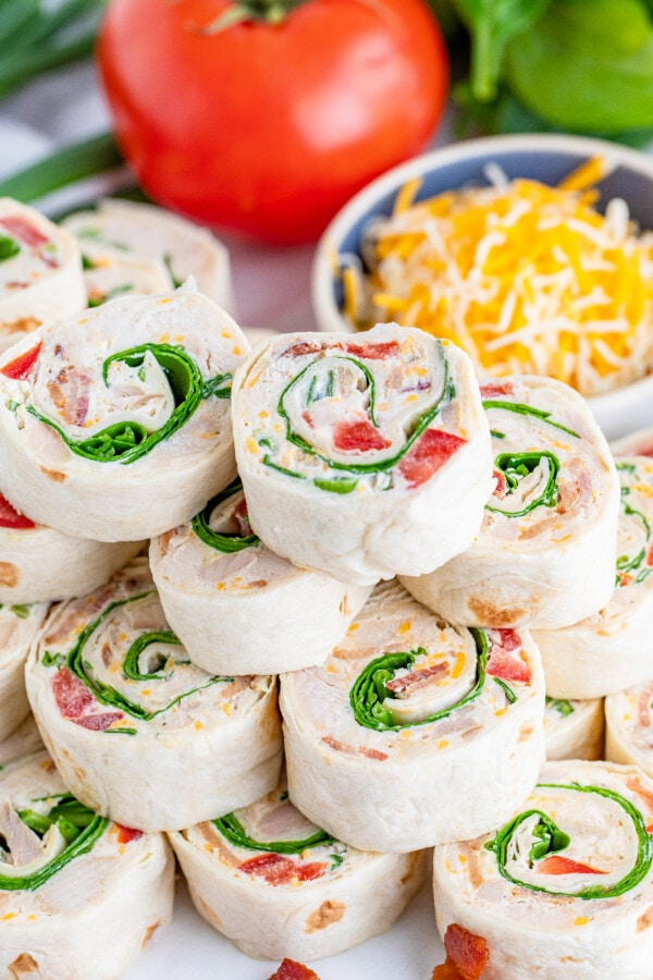 Closeup shot of chicken bacon ranch wrap slices on plate with bowl of shredded cheese and tomato in background