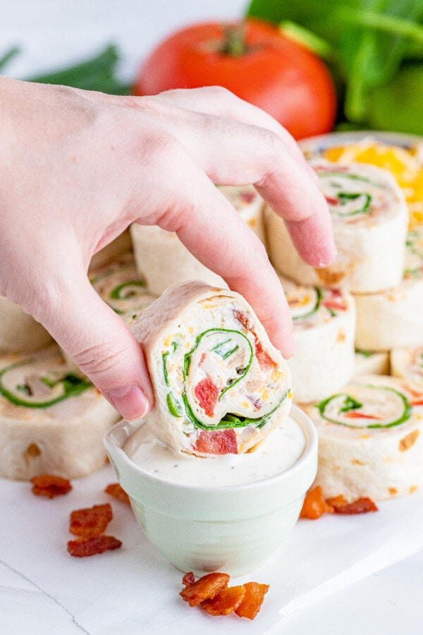 Hand dipping a slice of chicken bacon ranch wrap in ranch dressing