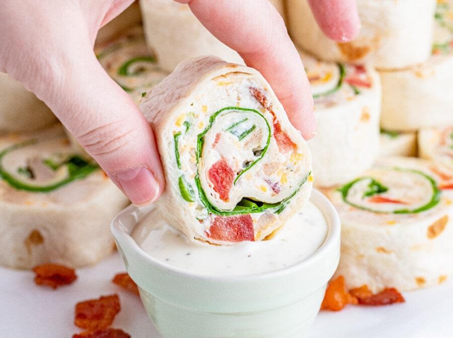 Closeup shot of dipping cheesy chicken bacon ranch pinwheels in ranch dressing