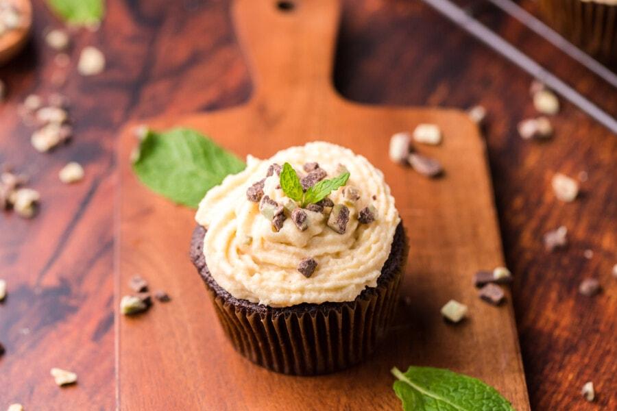 Chocolate mint cupcake with Bailey's Irish cream buttercream frosting on wood board.