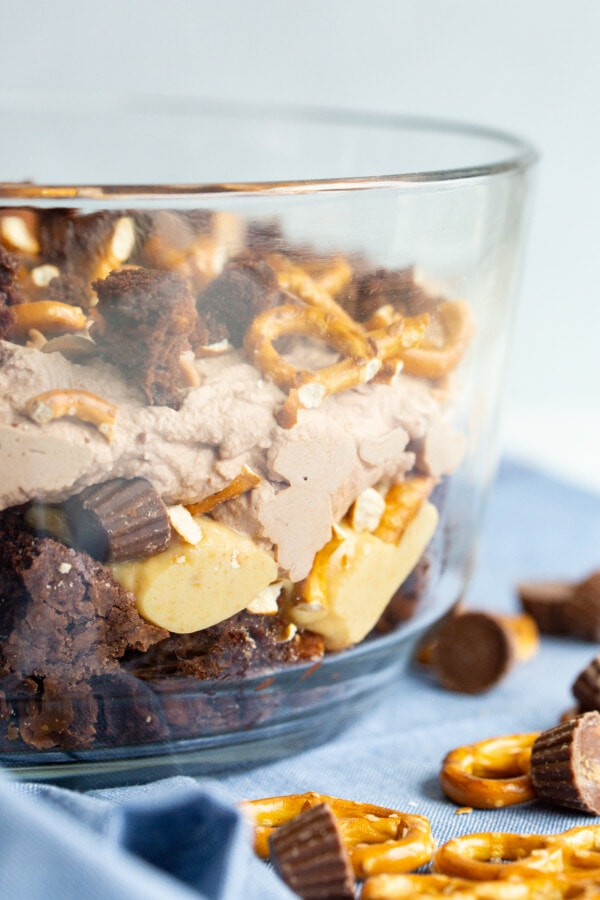 Bowl of peanut butter trifle in glass bowl on table with blue napkin