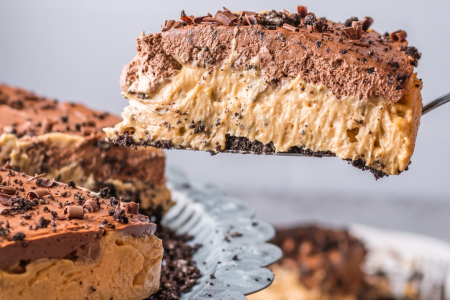 Closeup shot of no bake chocolate peanut butter pie slice on spatula with remaining pie below