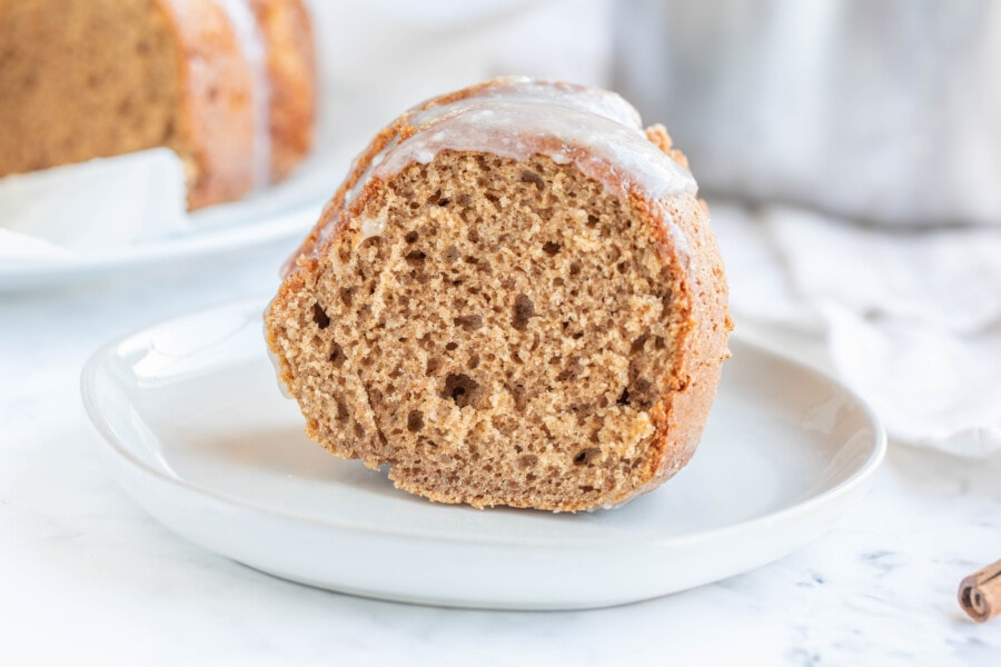 Slice of cinnamon or pumpkin spice bundt cake with cream cheese glaze
