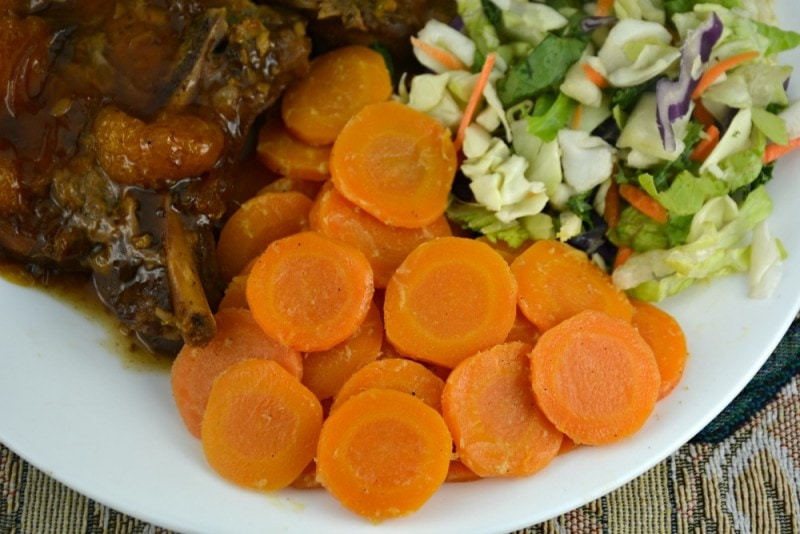 Glazed carrots on white plate with salad and beef. One of the best side dishes for ham.