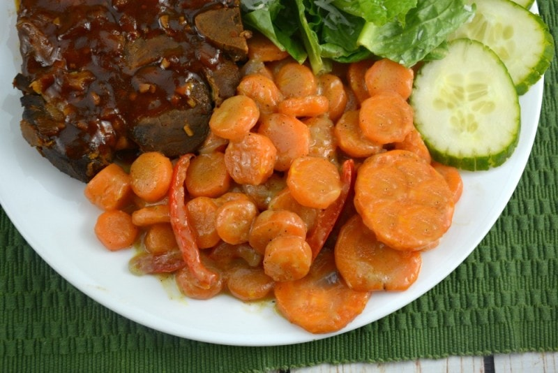 Carrots Lyonnaise with beef and salad on white plate. One of the best side dishes for ham.