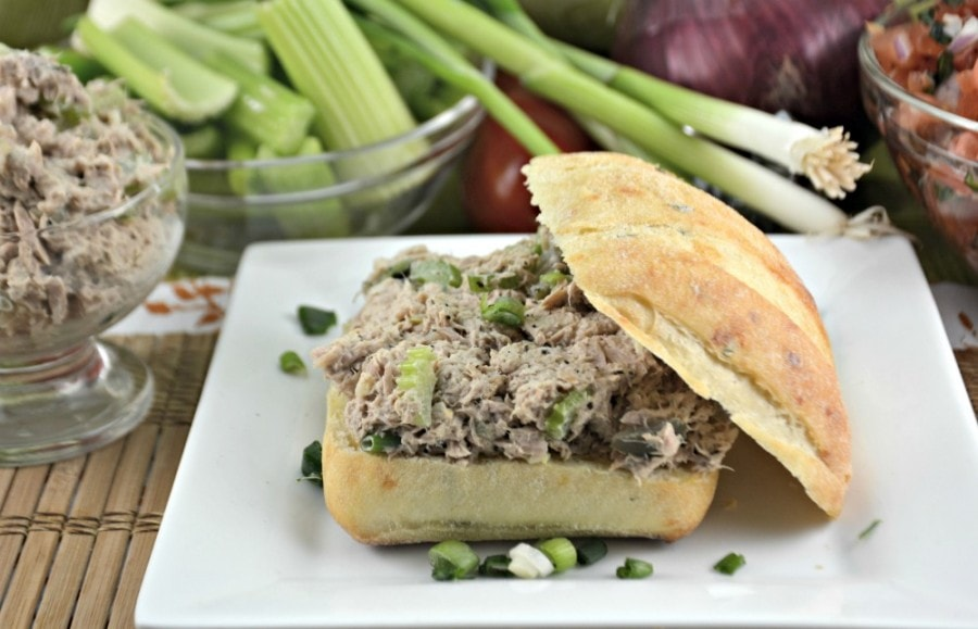 Closeup of open faced tuna salad sandwich from the side. There is tuna and celery in a bowl and some green onions in the background.