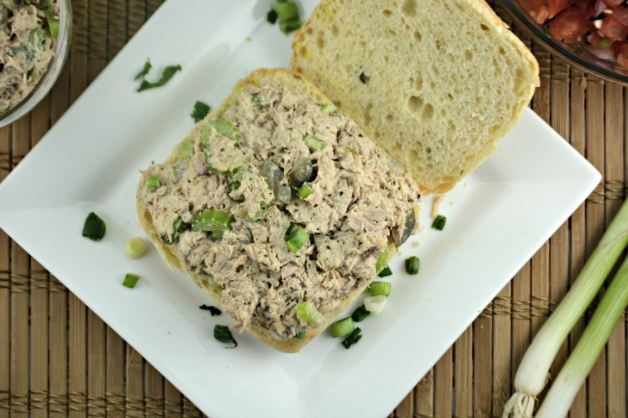 Overhead picture of open faced tuna salad sandwich on a bun with green onions.