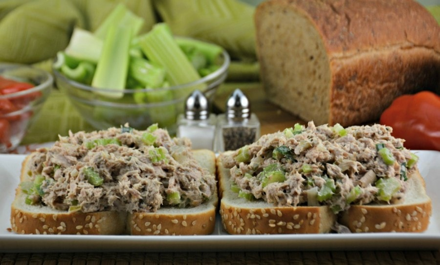 Two open faced tuna sandwiches, side by side on a plate with a loaf of bread and celery in background.