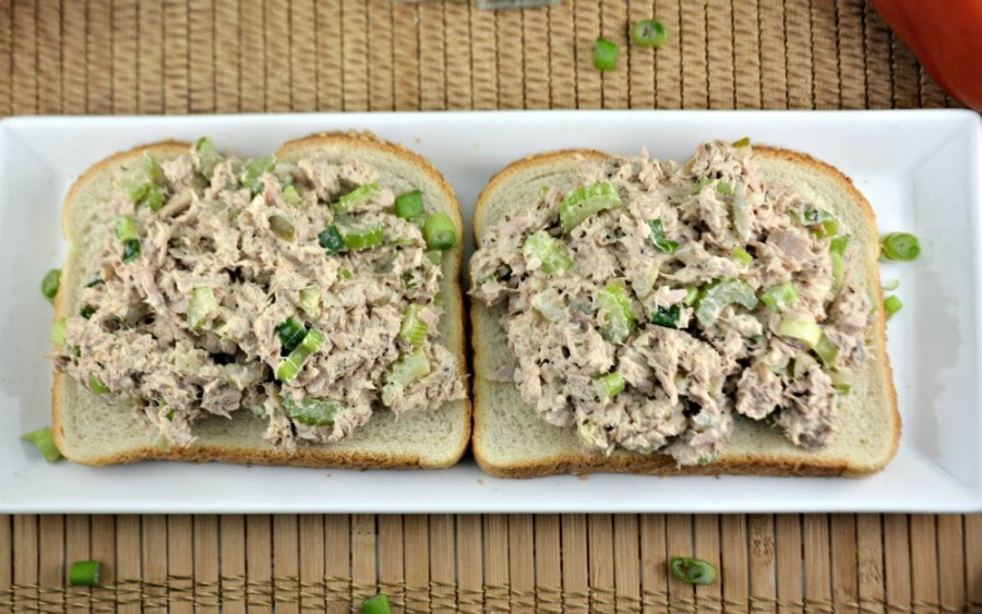 Overhead picture of two open faced tuna salad sandwiches on bread with green onions.
