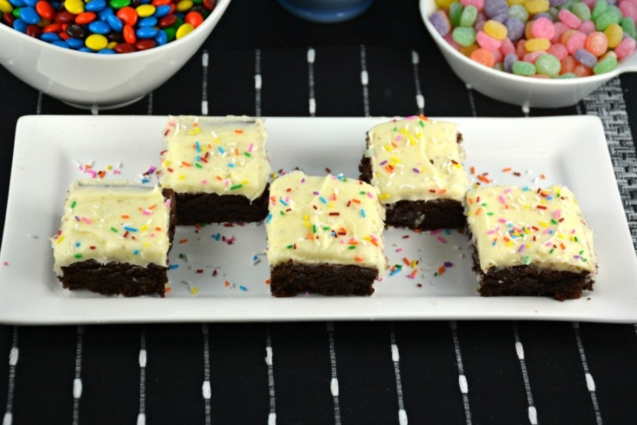 Peanut Butter Nutella Flavored Brownies with Cream Cheese Frosting cut into squares on a white plate on top of a black and white striped placemat.