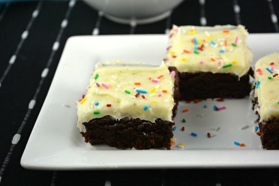 Closeup side shot of brownies on white plate.