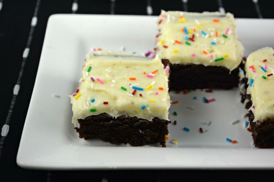 Brownies with Cream Cheese Frosting on a white plate with frosting and sprinkles.