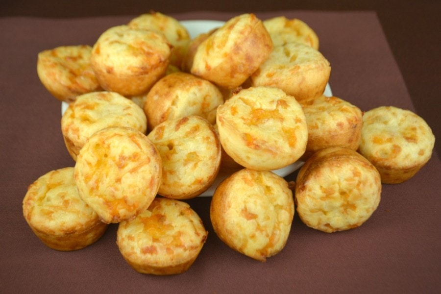 Brazillian cheese puffs stacked atop a white plate