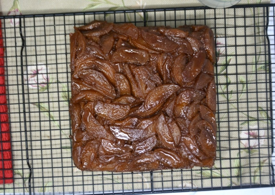 Overhead picture of entire cake upside down cooling on a rack.